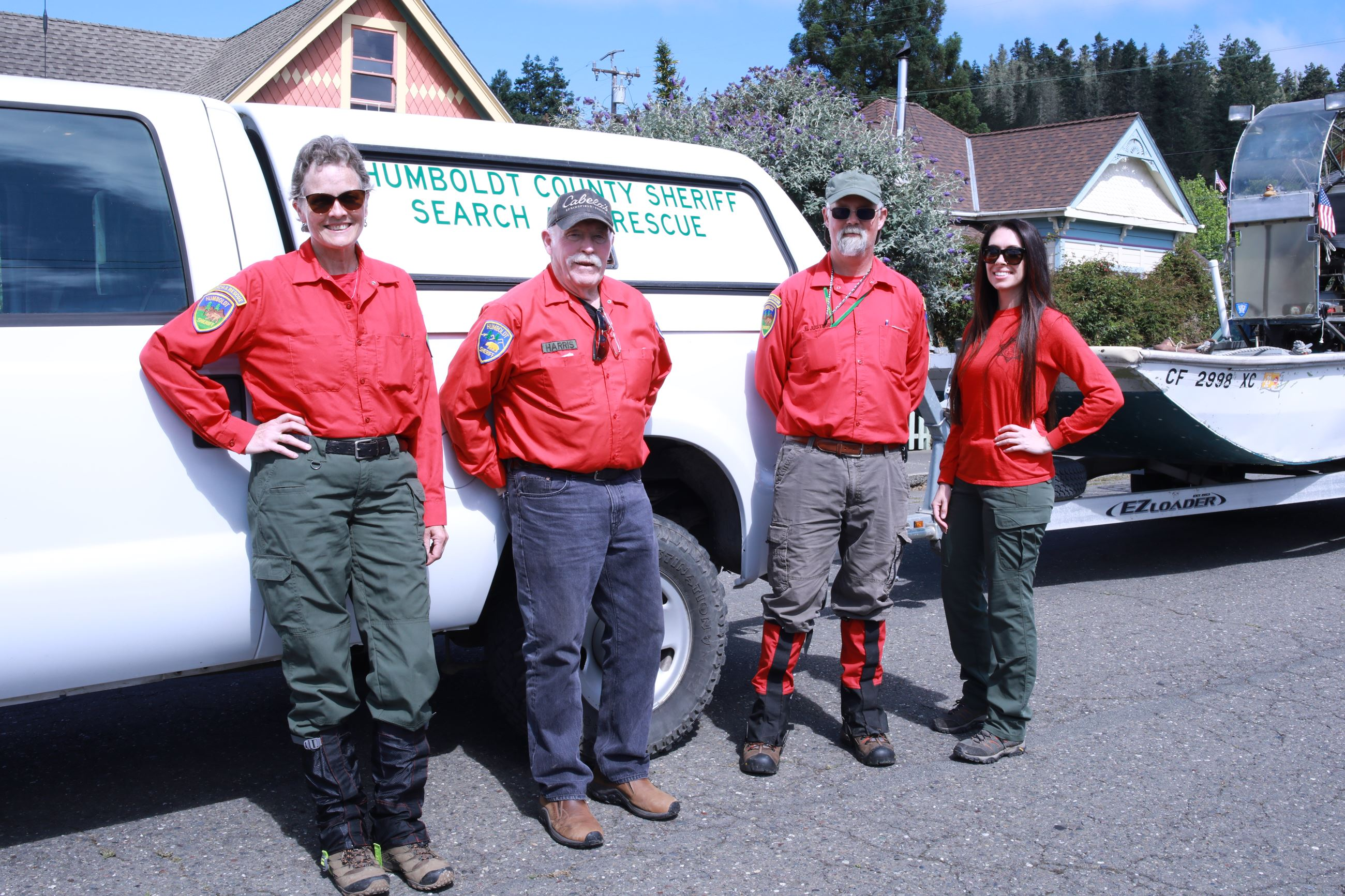 Sheriff's Search and Rescue Posse members stand in front of a rescue vehicle
