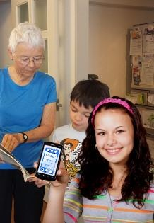 Image, a mom gets a text with grandma and son reading together in background.