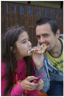 A dad and daughter share pizza outside a library.  The girl has a cell phone in hand.